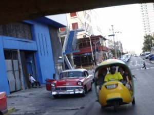 """The whole transportation scene in Cuba is a hoot. The little thing on the right is a """"Coco Cab"""" as it sort of resembles a coconut shell. This is a little plastic three person bench seat body that fits on the chassis of an old two-stroke scooter."""